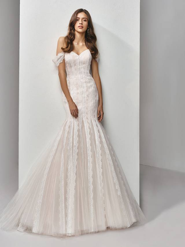 Code: Enzoani Beautiful BT19-28 Classically romantic with sweet, modern twists -- this full-length mermaid gown features delicate chantilly lace patterning atop soft tulle layers, with eye-catching lace strips draping down the length of the dreamy train. Complete with lovely off-the-shoulder sleeves, sweetheart neckline and invisible back zipper closure.Colour Options : Ivory/Latte  OR  Ivory/Ivory