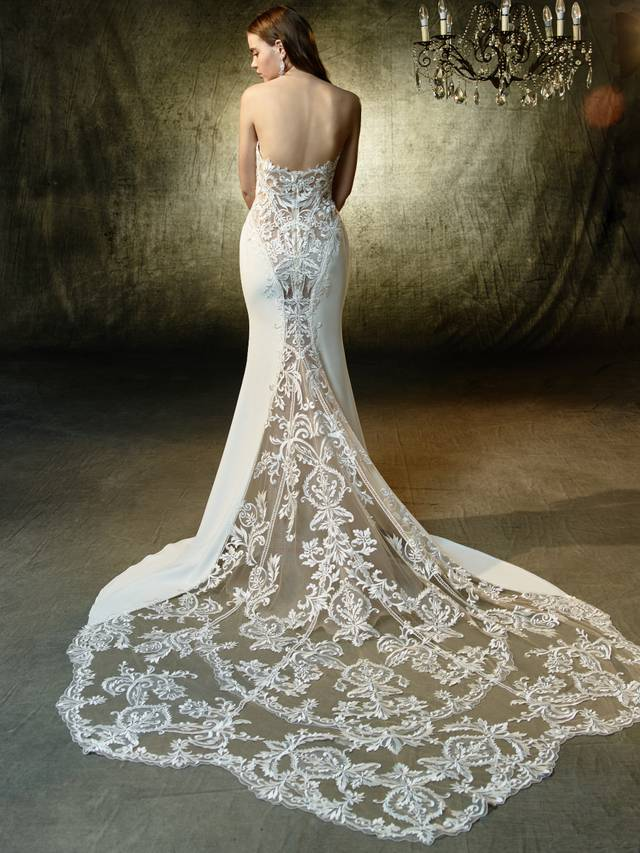 Code: Enzoani Blue Lainey A sumptuous mermaid gown constructed with sequin embroidered lace on soft stretch georgette. The strapless, illusion V-neckline complements the gorgeous back with a cascading, illusion lace train.Colour Options : Ivory/Nude  OR  Ivory/Ivory