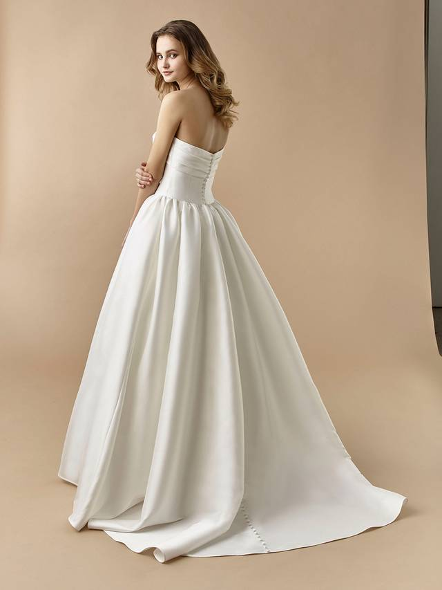 Code: Enzoani Beautiful BT20-08 Couture, chic, and comfortable to boot! This full length, A-line gown is sure to make a gorgeous statement with its tied bow and hidden pockets. Buttons gently line the back of the gown, trailing to the end of the train for an extra special touch.Colour Options: Ivory