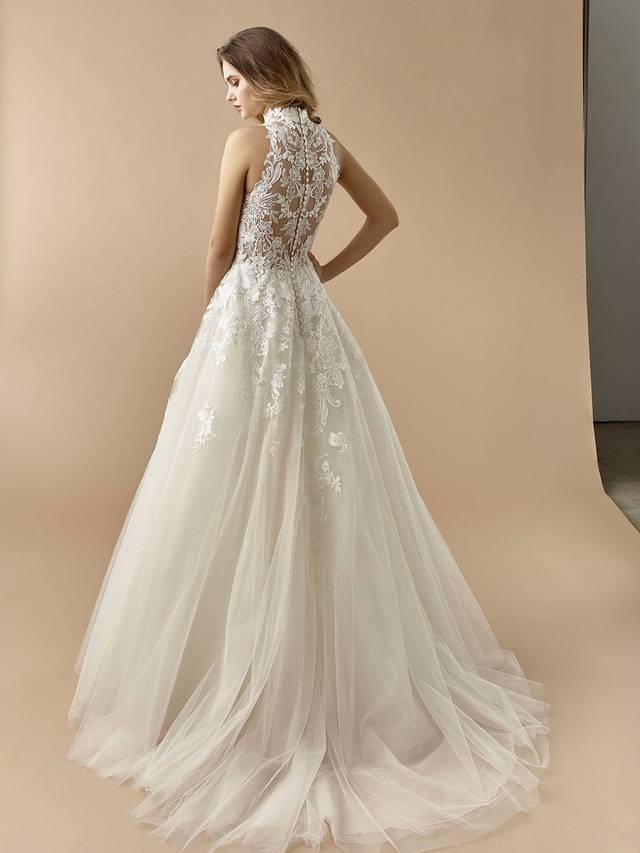 Code: Enzoani Beautiful BT20-13 This gorgeous A-line gown features the sweetest illusion lace bodice and high neckline to complement a matching illusion lace back. Finished with covered buttons and a dreamy, flowing tulle skirt adorned with lace appliques.Colour Options: Ivory/Nude  OR  Ivory/Ivory